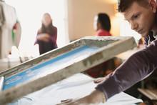 Man Using Silk Screen To Print...
