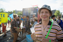 Portrait Smiling Young Man Holding Summer Music Festival Ticket Outside Entrance