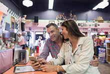 Mature Couple Using Cell Phone In Soda Fountain Shop