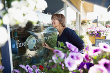 Woman Window Shopping At Flower Shop Storefront