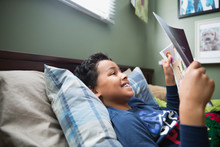 Smiling Boy Reading Comic Book In Bed