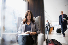 Businesswoman With Luggage Texting In Airport Lounge