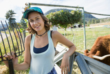 Portrait Smiling Female Farmer With Pitchfork On Sunny Cattle Farm