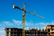 Construction crane against the blue sky. Construction of a multi-storey building