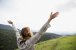 Exuberant woman with arms outstretched in remote rural field