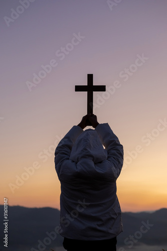 Obraz Silhouette human praying and holding christian cross for worshipping God at sunset background.Christian, Christianity, Religion copy space background. - fototapety do salonu