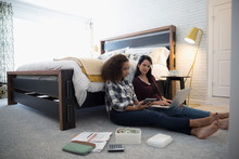 Mother With Laptop Teaching Daughter With Calculator Personal Finance Management In Bedroom