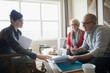Financial advisor discussing paperwork meeting with senior couple in living room