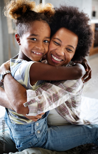 Obraz Portrait of a joyful mother and her daughter smiling and hugging - fototapety do salonu