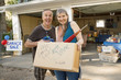 Enthusiastic couple holding box at garage sale