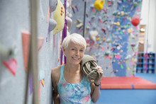 Smiling Woman With Rope At Rock Climbing Wall