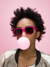 Portrait Playful African American Young Woman Blowing Bubble And Wearing Sunglasses Against Pink Background