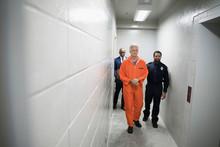Bailiff Walking Prisoner In Orange Jumpsuit Down Corridor In Jail