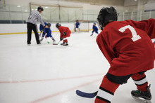Boy Ice Hockey Player Poised And Ready, Watching Face Off On Ice Hockey Rink
