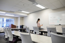 Businesswoman Reviewing Notes On Whiteboard In Empty Office Classroom