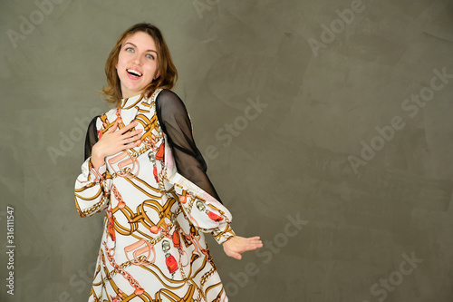 Photo Studio portrait of a pretty young Caucasian blonde girl in a light dress on a gray background