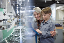 Grandmother And Grandson Looking At Model Naval Ship Exhibit In War Museum