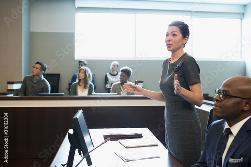 Photo Female prosecutor attorney talking in legal trial courtroom