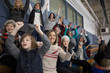 Mothers and children cheering in stadium bleachers at ice hockey game