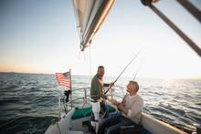 Male Friends Fishing On Sunset Sailboat