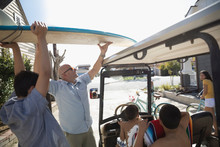Father And Son Loading Surfboard On Top Of Golf Cart In Summer Driveway