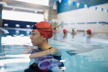 Serious Young Woman Swimmer Leaning On Swimming Pool Lane Divider