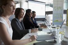 Businesswomen Smiling, Listening On Conference Panel