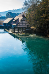 Germany, Early morning fog moving over water surface of blue pot or german blautopf in blaubeuren forest, a blue shiny natural source in warm sunlight on cold winter day