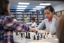 Focused Middle School Girl Students Playing Chess In Chess Club Library