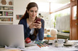 Female interior designer texting with cell phone at home office desk
