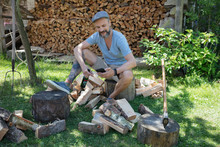 Man Drinking Beer, Chopping Wood And Texting With Cell Phone In Rural Yard