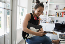 Teenage Girl Playing Electric Guitar And Texting With Cell Phone