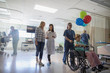Doctor talking to mother and nurse pushing boy patient in wheelchair in hospital