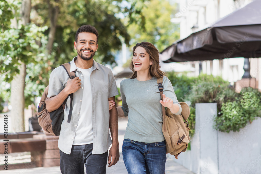 Fototapeta Beautiful happy couple summer portrait. Young joyful smiling woman and man in a city. Love, travel, tourism, students concept