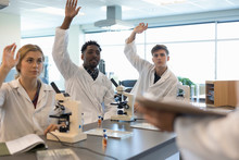 College Students Asking Question At Microscopes In Science Laboratory