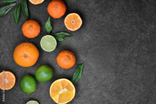 Fotografie, Obraz Fresh orange fruits and lime and knife with leaves