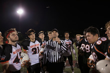 Teenage Boy High School Football Teams Watching Referee Perform Coin Toss On Football Field