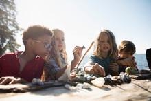 Curious Boy And Girl Friends Examining Rocks On Sunny Beach