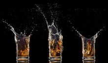 Glass Of Whiskey With Splash Isolated On Black Background
