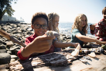 Portrait Smiling Boy With Friends Showing Rock On Sunny Beach