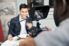 Man Vlogging, Videoing Friend Eating At Sidewalk Cafe With Video Camera