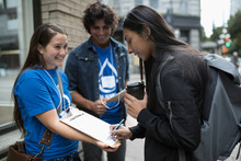 Political Young Adults Canvassing With Clipboard, Woman Signing Petition On Urban Sidewalk