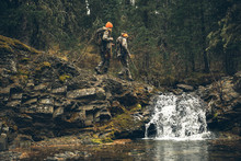 Mother And Daughter Hunters Carrying Hunting Rifles, Crossing Rocks Over Waterfall In Forest