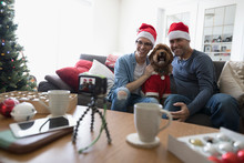 Father, Son And Dog In Santa Hats And Costume Taking Selfie In Christmas Living Room