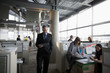Businessman walking and using digital tablet in open plan office