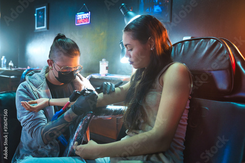 Young Woman Getting Tattoos In Beauty Parlor With Tattooist Working Canvas Print