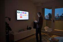 Senior Man Using Smart TV Apps...