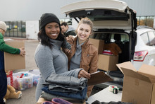 Portrait Smiling, Enthusiastic Young Female Volunteers Loading Donations Into Car In Parking Lot