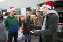 Young Adult Volunteers In Santa Hats Meeting In Parking Lot