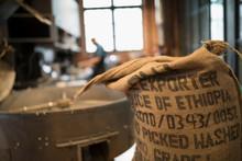 Burlap Sack Of Ethiopian Coffee Beans Next To Coffee Roaster